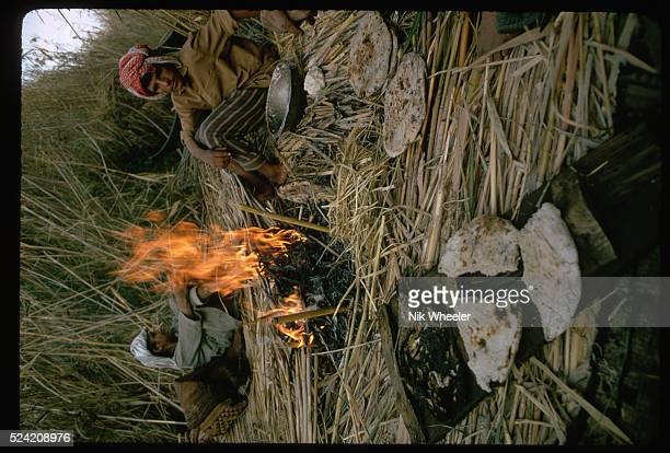 Bread and fish sit next to a cooking fire in a Marsh Arab village Iraq   Location The Marshes near Nasiriya Iraq