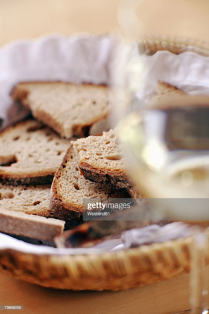 Bread basket and glass of wine, close-up, (differential focus) : Stock Photo