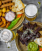 bread croutons with garlic and other snack with glass of beer on table in bar