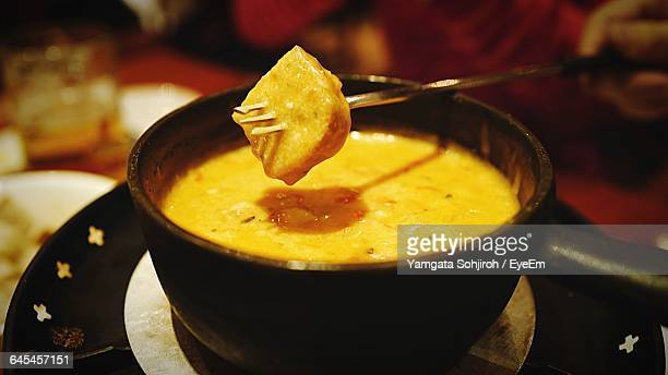 Bread Dipped In Cheese Fondue With Fondue Fork