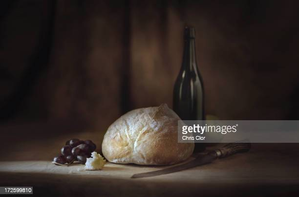 Bread, fruit, wine and cheese on table