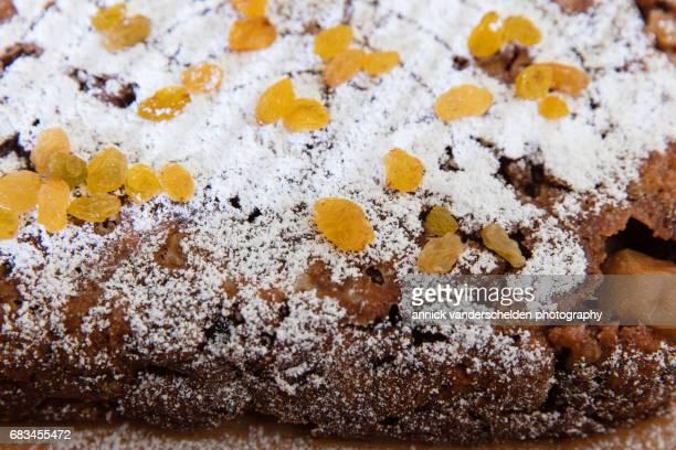 Bread pudding with icing sugar and raisins as garnish.