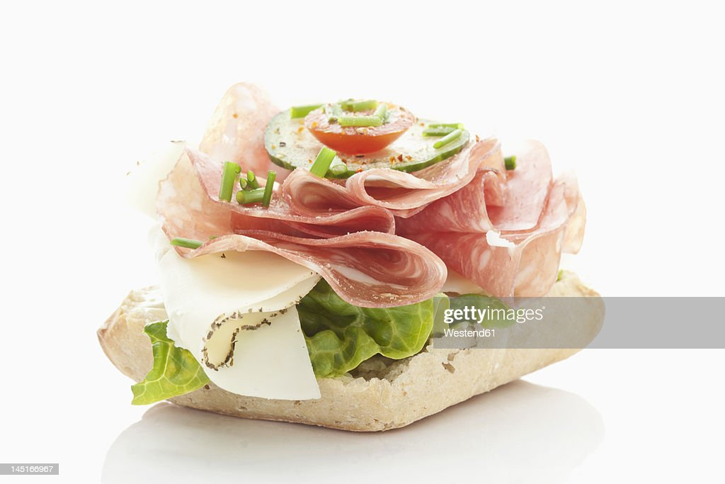 Bread roll with salami, cheese, tomatoes, lettuce on white background