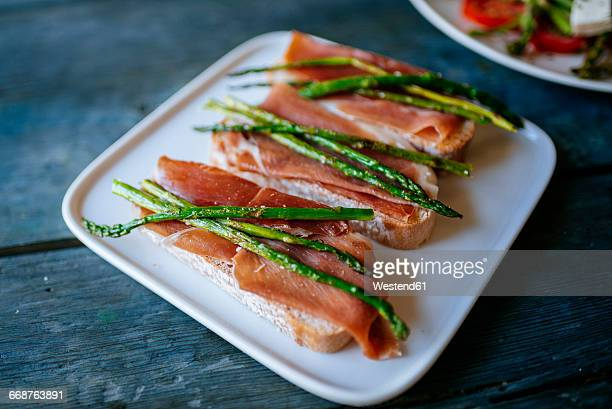 Bread slices with cured ham and grilled green asparagus on platter