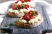 Bread slices with ricotta cheese and, sun dried tomatoes in olive oil