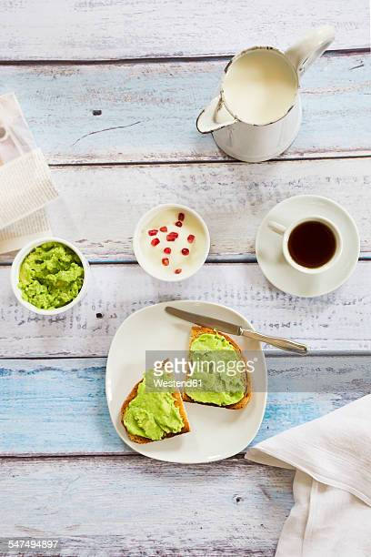 Bread with avocado cream, yogurt with pomegranate seeds and cup of coffee