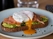 Rye Bread with smashed avocado, smoked salmon and poached egg with yolk flow