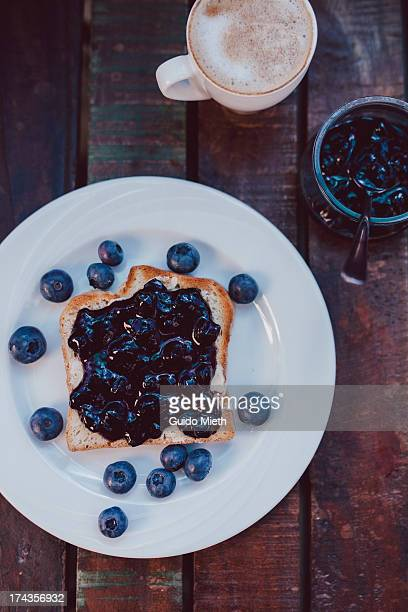 Bread with blueberry jelly and coffee.