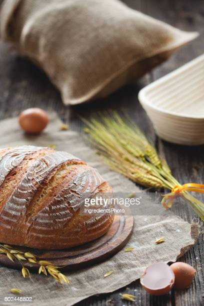 Bread with wheat and dough shape on wooden table. Bag of flour on background.