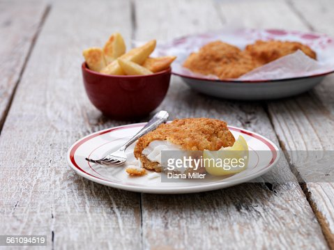 Breaded chunky cod with bowl of french fries on wooden table