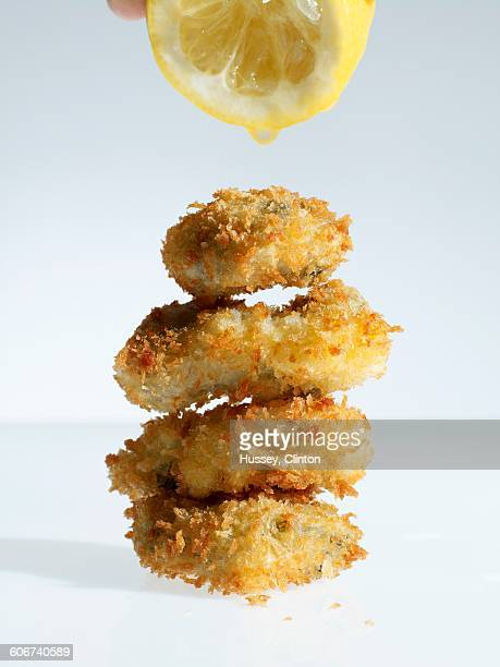 Breaded oysters being drizzled with lemon juice