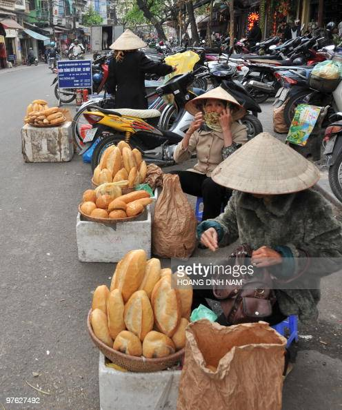 Breads vendors sit behind their baskets of breads on a street in downtown Hanoi on March 10 2010 Vietnam beat its annual inflation target of seven...