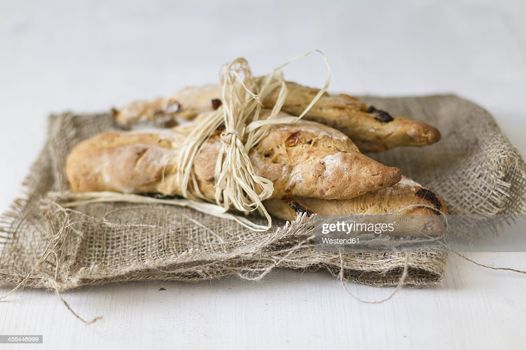 Breadsticks tied up with straw on jute sack, close up : Stock Photo