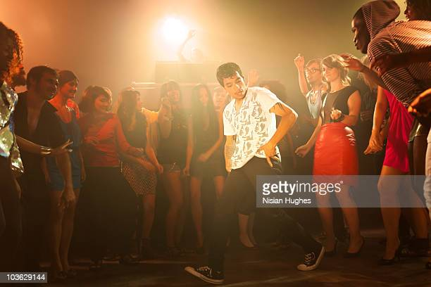 A break dancer surrounded by crowd at a club