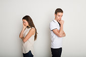 Break up, divorce. Upset young couple standing back to back after quarrel, thinking about relationship, copy space