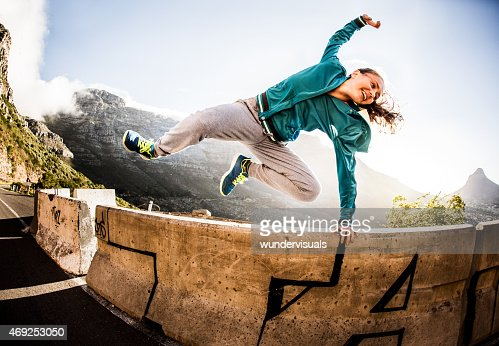 Breakdancer full of vitality jumping over a wall parkour style