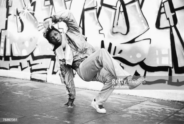 A breakdancer in action against a graffiti backdrop circa 1983