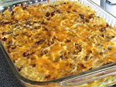 Breakfast casserole in glass baking dish, featuring sausage, cheese, egg and hash browns.