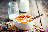 Breakfast cereal wheat flakes in bowl and milk bottles on wooden kitchen table