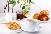 Breakfast - cup of coffee, croissants, jam and fruits on white table.