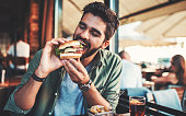 Young man sitting in a cafe and enjoying in breakfast. Food, lifestyle concept