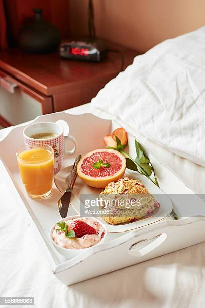 Breakfast in bed with homemade rhubarb scones, strawberry butter, grapefruit, fresh juice and coffee