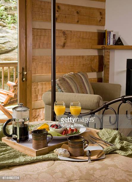 Breakfast items on wooden tray on bed