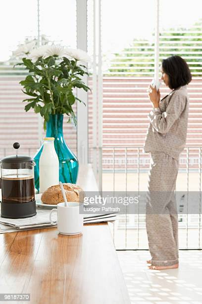 Breakfast on a kitchen counter and a women in pajamas drinking coffee