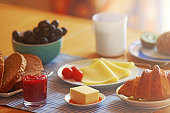 breakfast with croissant, jam, bread, cheese and fruit, back lit