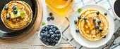 Breakfast - pancakes with blueberries, white wood background