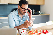 Attractive young man in denim shirt typing message on his phone while having breakfast at home