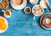 Breakfast setting over blue table with copy space border. Yogurt, pumpkin granola, bagel, butter. Top view. Flat lay