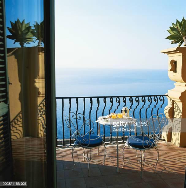 Breakfast table on balcony by sea