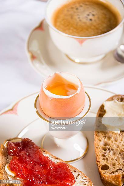 Breakfast table with black coffee, boiled egg and bread with jam
