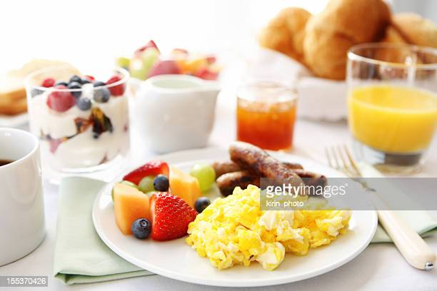 Breakfast table with eggs, fruit, and sausages