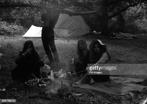 Breakfast toast and coffee around the fire for three 16 year old girls who were among the tens of thousands of young people encamped at Woodside Bay...