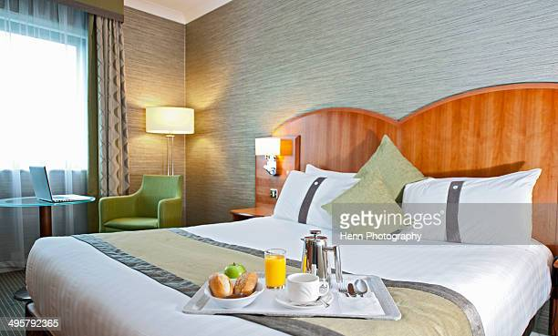 Breakfast tray on the side of a bed in a hotel room