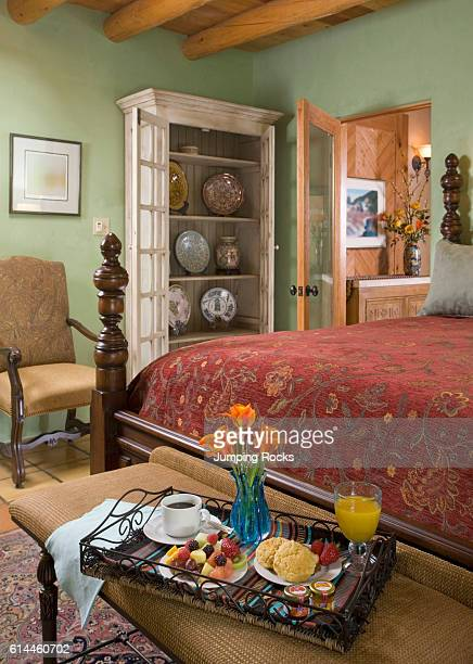 Breakfast tray with vase of flowers at end of mahogany four poster bed Santa Fe New Mexico
