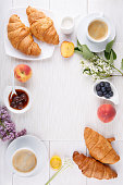 Breakfast - two cups of coffee, croissants, jam, honey and fruits on white table.  Top view. Copy space.