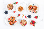 Breakfast with belgian waffles, muesli, fresh fruits on white background. Flat lay, top view