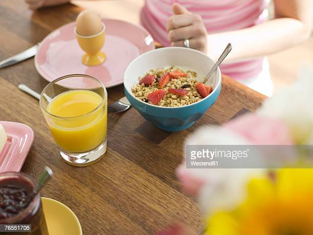 Woman sitting at dining table having breakfast, mid section