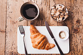 Breakfast with coffee and butter croissant on wooden table