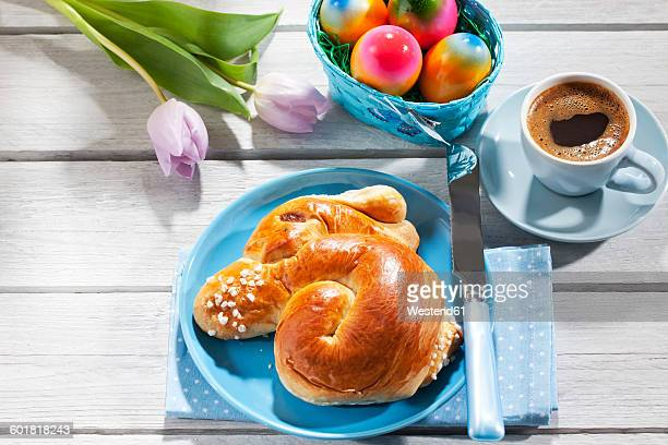 Breakfast with coloured Easter eggs, cup of coffee and Easter pastry