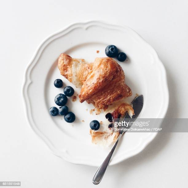 Breakfast with croissant and blueberries.