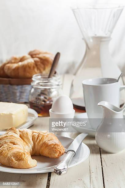 Breakfast with croissant, egg, coffee, honey and butter