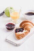 Breakfast on white wooden background - croissant, jam,  orange juice and coffee