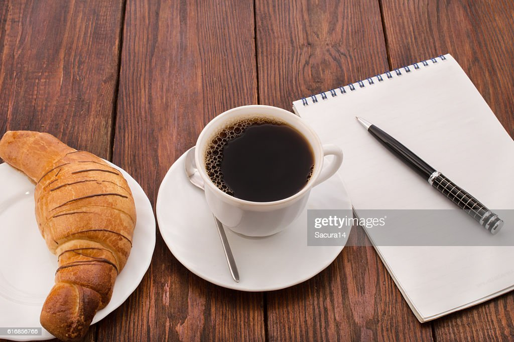 breakfast with cup of black coffee, croissants and notebook : Stock Photo