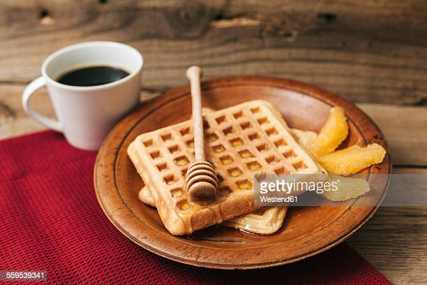 Breakfast with cup of coffee, waffles, honey and orange slices