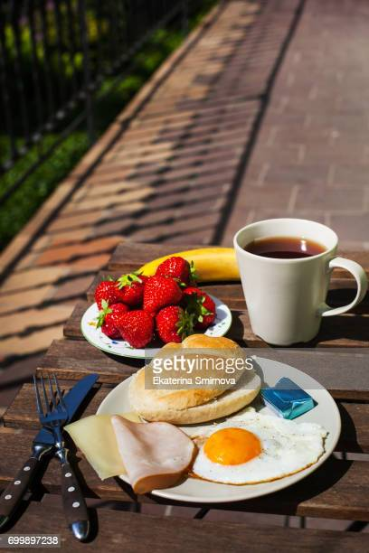 Breakfast with fried egg, ham, cheese, strawberry and coffee on balcony