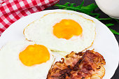 Breakfast with fried eggs, bacon and rucola salad on dark stone background.